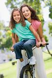 Woman and young girl on a bike outdoors smiling