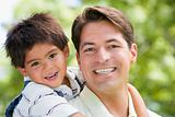 Man and young boy embracing outdoors smiling