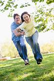 Couple running outdoors holding hands and smiling