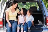 Woman with two children sitting in back of van smiling