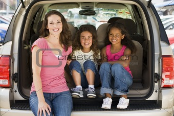 Woman with two young girls sitting in back of van smiling