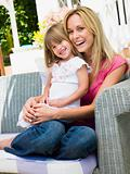 Woman and young girl sitting on patio laughing