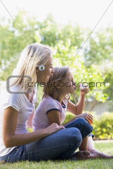 Woman and young girl outdoors blowing bubbles smiling