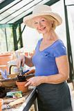 Woman in greenhouse putting soil in pot and smiling
