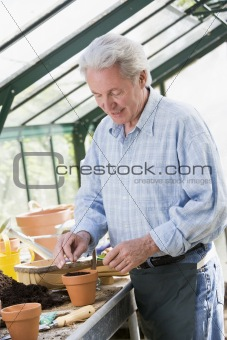 Man in greenhouse putting seed in pot smiling