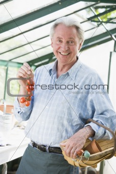 Man in greenhouse holding cherry tomatoes smiling