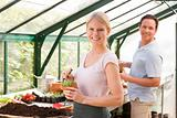 Couple in greenhouse raking soil in pots smiling