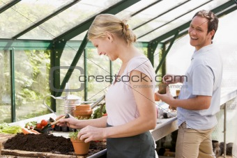 Couple in greenhouse putting soil in pots smiling