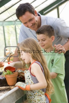 Man in greenhouse helping two young children putting soil in pot