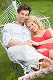 Couple relaxing in hammock smiling