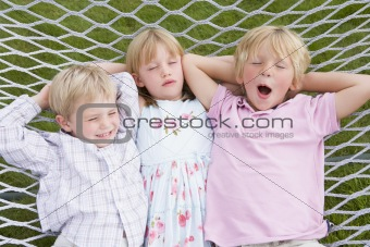 Three children relaxing and sleeping in hammock