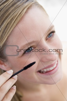 Woman with mascara wand smiling