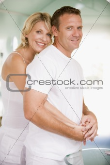 Couple in bathroom embracing and smiling