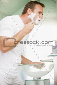 Man in bathroom shaving