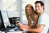 Couple in home office with computer smiling