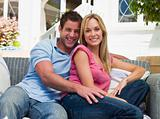 Couple sitting outdoors on patio smiling