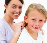 Portrait of happy young mother combing hair of daughter