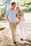 Couple walking outdoors arm in arm smiling