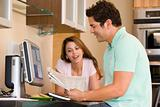 Couple in kitchen with computer and newspaper smiling