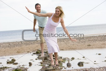 Couple at the beach walking on stones and smiling