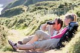 Couple on cliffside outdoors using binoculars and smiling