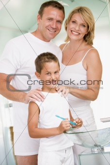 Couple in bathroom with young boy brushing teeth