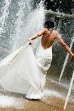 Beautiful young bride playing in a waterfall on her wedding day.