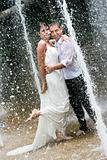 Bride and groom dancing under a water fountain on their wedding day.