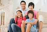 Family sitting on staircase smiling