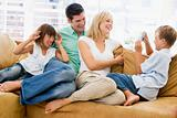 Family sitting in living room with digital camera smiling