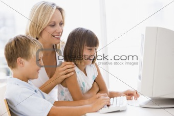 Woman and two young children in home office with computer smilin