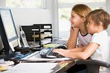 Young boy and young girl in home office with computer smiling