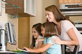 Woman and two young girls in kitchen with computer smiling
