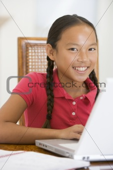 Young girl with laptop in dining room smiling