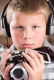 Young boy wearing headphones in bedroom holding many electronic