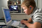 Young boy in bedroom using laptop and listening to MP3 player