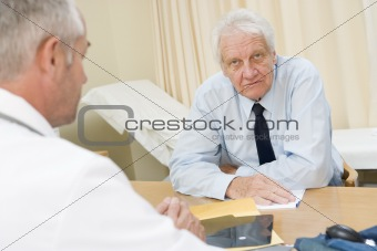 Man in doctor's office frowning