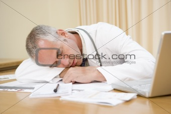 Doctor with laptop sleeping in doctor's office
