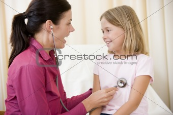 Doctor giving checkup with stethoscope to young girl in exam roo