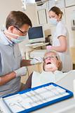 Dentist and assistant in exam room with woman in chair