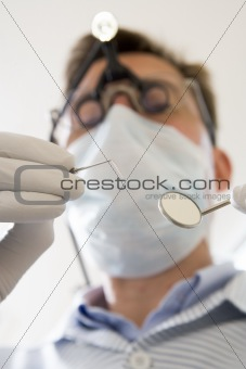 Dentist holding pick and mirror