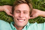 Man lying on grass smiling