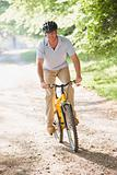 Man outdoors riding bike smiling