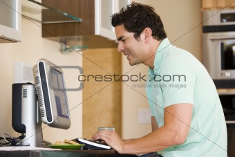 Man in kitchen using computer and smiling