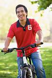 Man outdoors on bike smiling