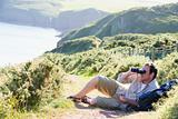 Man relaxing on cliffside path using binoculars