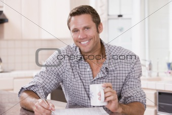 Man in kitchen reading newspaper and smiling