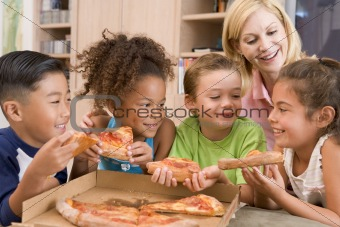 Four young children indoors with woman eating pizza smiling