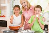 Woman and two children in kitchen baking and smiling