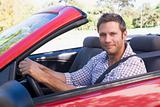 Man in convertible car smiling